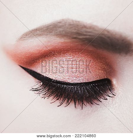 Closed female eye with arrow closeup. A beautiful female eye with an arrow. Eye close-up. Eye with makeup. Long eyelashes on the closed eye. Mascara on the eyelid