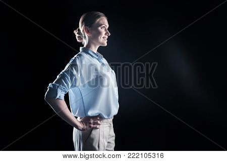 Being optimistic. Joyful pleasant young woman standing half face and smiling while being in a good mood