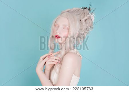 Blonde girl portrait with curly hair with pale skin in a retro dress. Woman portrait. Stylish female portrait. Portrait of a model in studio. Portrait of a girl on a blue background. Beauty portrait