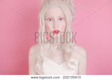 Blonde girl portrait with curly hair with pale skin in a retro dress. Woman portrait. Stylish female portrait. Portrait of a model in studio. Portrait of a girl on a pink background. Beauty portrait