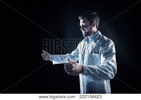 Pleasant job. Happy nice male scientist holding a virtual device and smiling while enjoying his job