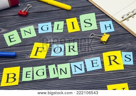 Education and Study concept: English for beginners inscription and stationary on a black wooden table, top view