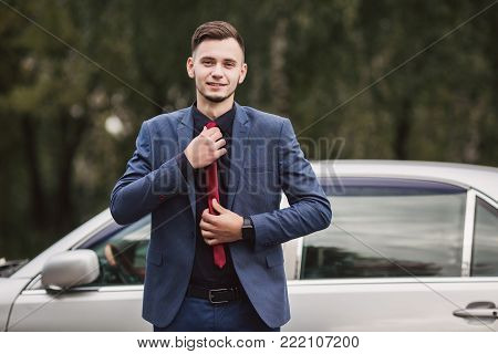 Luxury business man in a dark business suit near car. Success in the difficult task. Luxury business man in a dark suit. Luxury man. Luxury in business. Achieve luxury in work. The man enjoys luxury.