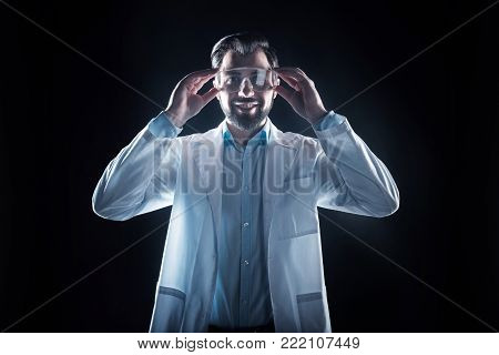 Safety equipment. Positive nice cheerful scientist smiling and wearing his glasses while looking in front of him