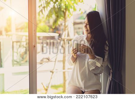 Asian woman drinking coffee in the morning breakfast in window bedroom fresh start the day happiness relax at home healthy lifestyle concept