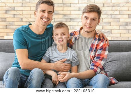 Male gay couple with adopted boy on sofa at home