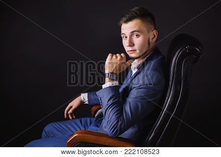 Successful businessman in business suit with a tie on dark background. Stylish businessman. Confident businessman on the background of the black wall. Young businessman. A focused businessman on the success. Successful businessman concept