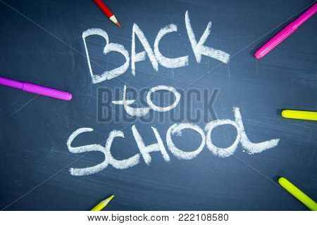 Education concept: Back To School inscribed on a black chalkboard with colored pencils, close up, top view