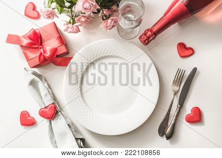 Valentines Day Dinner With Table Place Setting With Red Gift, Glass For Champagne, A Bottle Of Champ