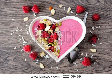 Healthy raspberry smoothie in a heart shaped bowl with superfoods. Above scene on a wood background.