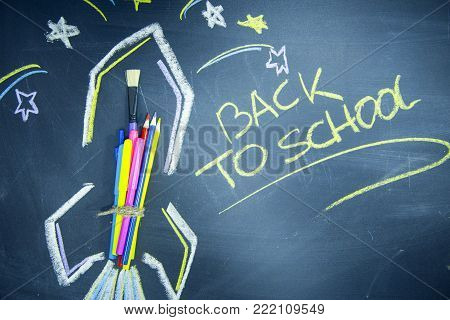 Education concept: Creative learning. Space rocket ship made of colored pencils on a black chalkboard and Back To School inscribed with a yellow chalk