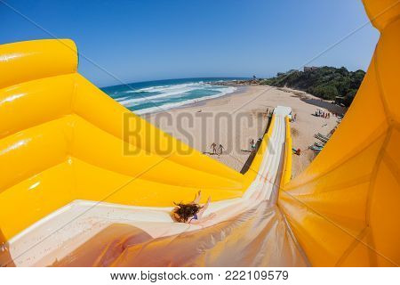 Beach Girl action thrill jump ride down high inflatable water slide summer holidays landscape.