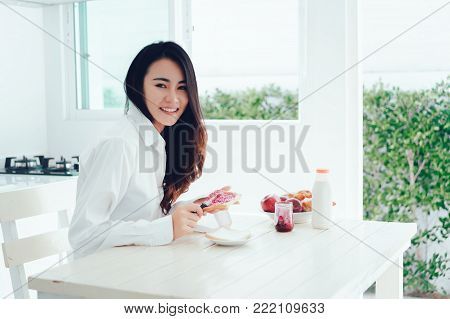 Asian woman slice jam bread in the morning and eating apple fruit,coffee healthy food breakfast meal in kitchen room fresh start the day at home healthy lifestyle concept