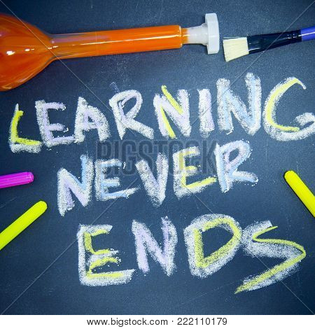 Education concept: Learning Never Ends inscribed with colored chalks on a black chalkboard, pencils and a beaker with orange liquid, top view, close up, square crop