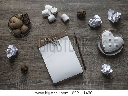 on a wooden background lies a craft notepad scrapbooking plate cookie heart pencil brown marshmallow nuts lump paper mint