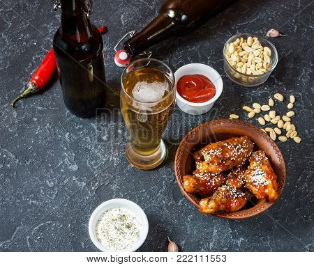 Buffalo style chicken wings served with cold beer on stone background