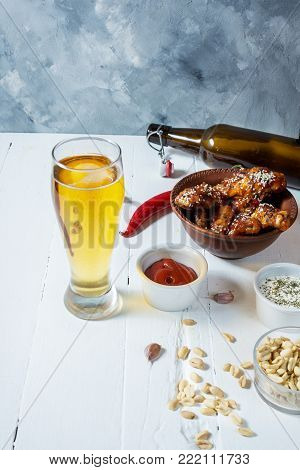 Buffalo style chicken wings served with cold beer on white wood background.