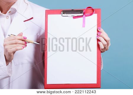 Doctor with diagnosis. Part body of female specialist holding red folder with disease files. Pink breast cancer awareness ribbon.