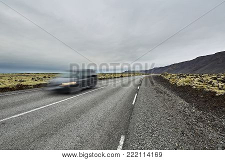 Route with orange roadside pillars between the green fields and mountains on the background of the cloudy sky in Iceland. There is a blurry car in motion on the driveway. Horizontal.