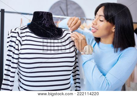 Attentive tailor. Qualified experienced attentive tailor looking at the sleeve of a striped blouse while finishing a stitch on it