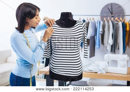 Careful tailor. Young experienced cheerful tailor looking concentrated while standing next to the mannequin and making the last stitch on a beautiful striped blouse