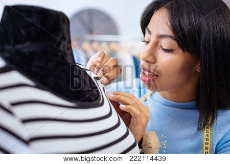 Very careful. Calm attentive careful tailor feeling concentrated while checking the stitches on a ready blouse before giving it to a client
