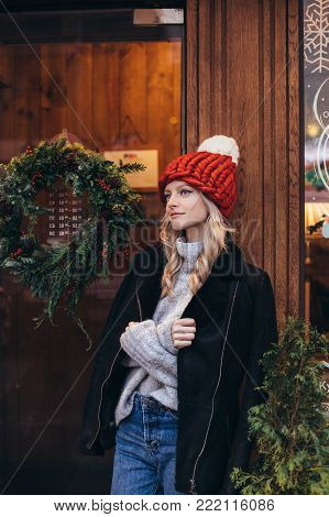 Young blonde woman in red knitted hat with white pompon, grey sweater, black jacket and blue jeans make posing with Christmac cafe window on the background