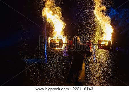 A stunning fire flame show against a dark night. A fire man in a chemical protection suit and a gas mask plays with flame. Fire show. Man in flame. Flame of fire in the night