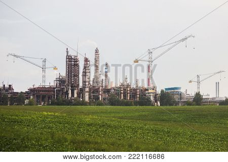 A large fertilizer processing plant factory. Pollution of air and atmosphere by factory. The pipes of factory emit dirty smoke. A big factory on the street. Pipe factory. Factory for processing of fertilizers