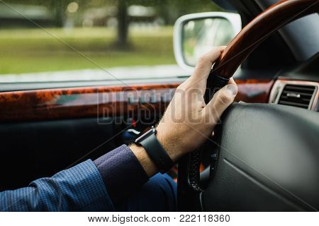 Successful business man in a dark business suit in the car. Stylish man in car. Young driver in car. Sitting behind the wheel of a new car. A man is smiling in the car. To drive car. Hands on the wheel of a car