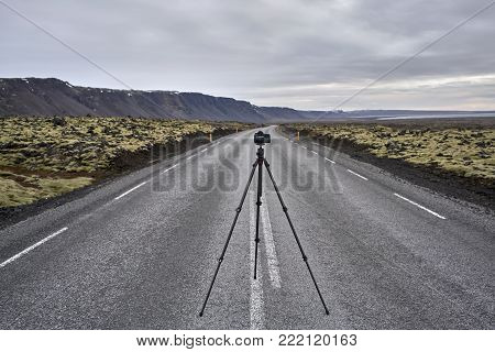 Camera on the tripod on the roadway with orange roadside pillars between the green fields and mountains on the background of the sea and cloudy sky in Iceland. Closeup. Horizontal.