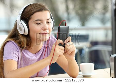 Relaxed teenager wearing headphones is listening to music holding a smart phone in an hotel bar