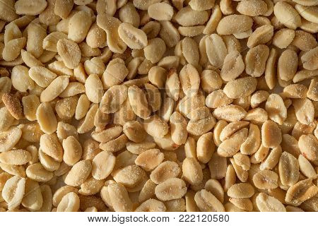 Peanuts sprinkled with salt, top view. Nutty background.