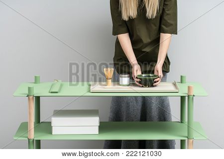 Pretty girl holds an emerald bowl on the green metallic-wooden stand on the gray wall background in the studio. On the stand there is white box, colorful metal supports, jar, tea whisk. Horizontal.