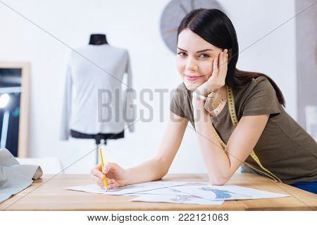 Pleasant work. Creative talented skilled worker of a professional atelier looking satisfied with her drawing while standing next to the table with her chin resting on her hand