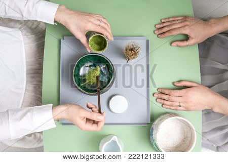Couple of girls preparing a chinese matcha green tea on the green metal table indoors. One woman puts tea powder into the colorful bowl. On the table there is a tea whisk and white jug with water.