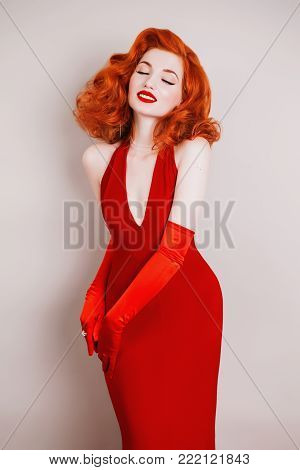 Red-haired retro woman with curly hair in red retro dress and long retro gloves. Retro girl is dressed in retro style with fur. Retro woman with pale skin and lred hair