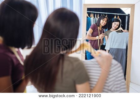 Fashionable dress. Positive young skilled tailor standing in front of a big mirror while showing a ready dress to her young demanding client and feeling satisfied with it