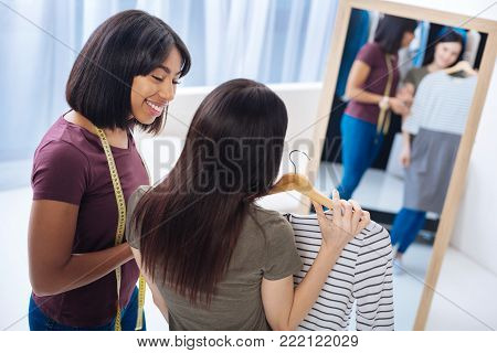 Helpful person. Cheerful attentive skilled tailor standing in front of a big mirror and looking at her pretty young satisfied client with a beautiful dress in her hands