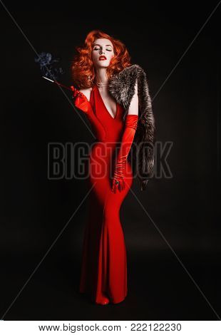 Red-haired vintage woman with curly hair in red vintage dress and long vintage gloves smoke. Vintage girl is dressed in vintage style with fur and the mouthpiece with a cigarette. A vintage woman with pale skin and red hair