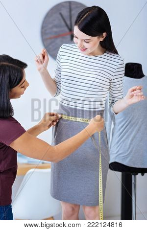 Appropriate size. Smart experienced skilled tailor feeling satisfied with the correct size of a striped dress while measuring her cheerful curious client