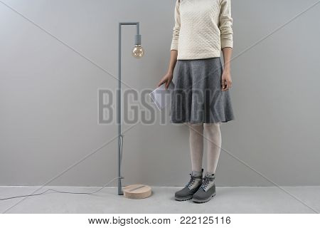 Delightful girl stands next to the long lamp with edison bulb on the gray wall background in the studio. She wears a beige pullover, gray skirt, tights and boots. Woman holds a book in the right hand.