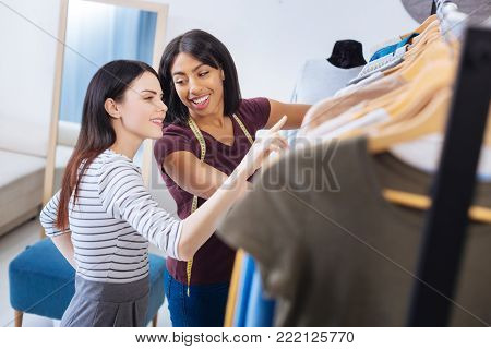 Friendly communication. Polite friendly young tailor looking attentive while standing in a popular atelier with a cheerful client and choosing new clothes