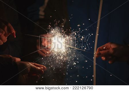 Friends holding beautiful sparklers in celebration of the new year.