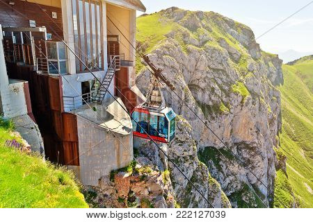 FUENTE DE,SPAIN - JULY 10, 2016: The cabin of the ropeway Teleferico Fuente De. The cabin arrives to the station at mountain top in beams of the sunset sun.