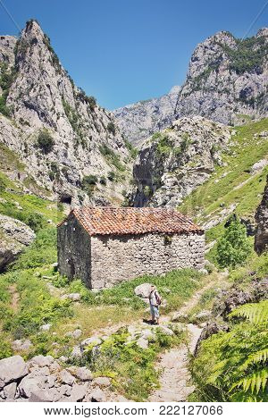 Picos De Europe, Spain - July 9, 2016: The Ancient Stone Shed With A Tile Roof In Mountains. The Man