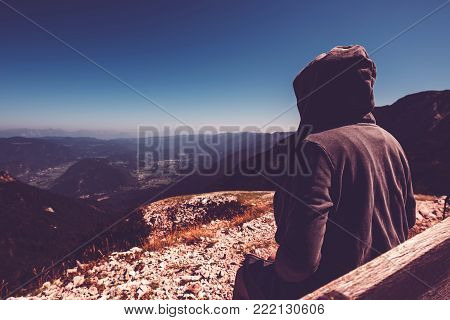 Mountain hiker at high viewpoint looking at the valley. Female tourist person in hooded jacket at mountain top enjoying the view,  ultra violet toned shadows