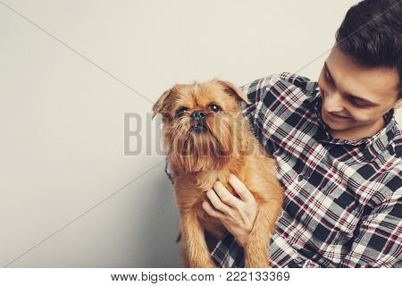 Man Holds Teddy Bear On A Light Blue Background, Copy Space. Pretty Toy Concept. Man Hugs Cute Toy B