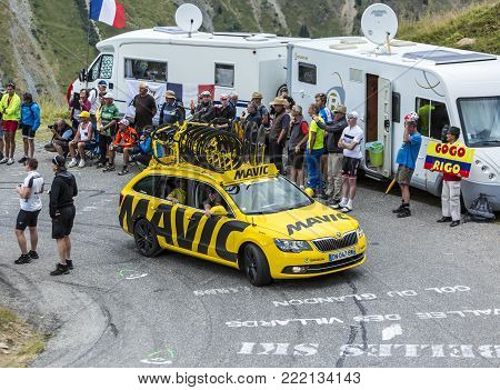 Col du Glandon, France - July 24, 2015: The yellow service car of Mavic driving on the road to Col du Glandon in Alps, during the stage 19 of Le Tour de France 2015.