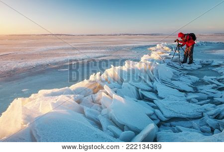 Photographer take pictures on the river coast in winter time